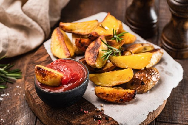 Chunky baked potato wedges with ketchup.