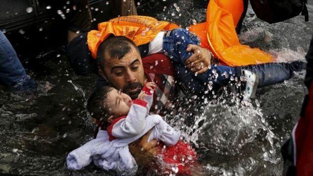 Un refugiado sirio sujeta a su hijo mientras lucha por salir de su bote en la isla griega de