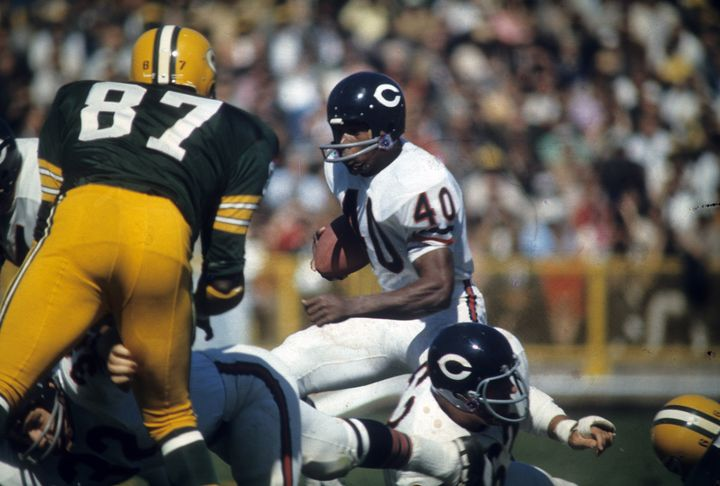 Gale Sayers tries to elude the Green Bay Packers' Willie Davis in a circa-1960s NFL game.