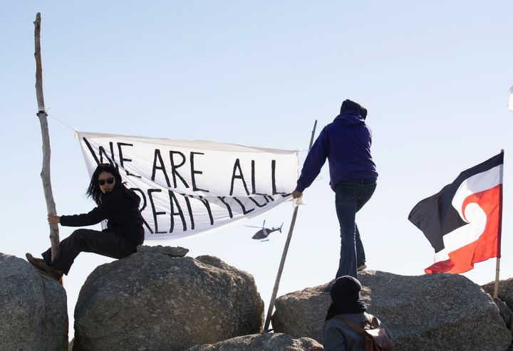 """Sipekne'katik First Nation community members waved a flag that said, """"We are all treaty people,"""" while a coast guard helicopter hovered in the background in Saulnierville, N.S., on Sept. 20, 2020."""