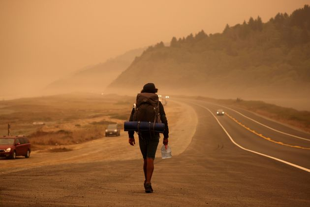 A man walks along the Redwood Highway by the Pacific Ocean coast as smoke from wildfires covers an area...