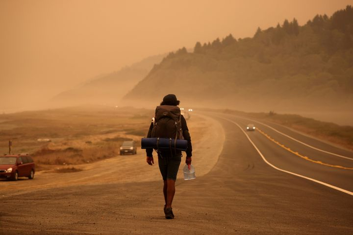 A man walks along the Redwood Highway by the Pacific Ocean coast as smoke from wildfires covers an area near Orick, Californi
