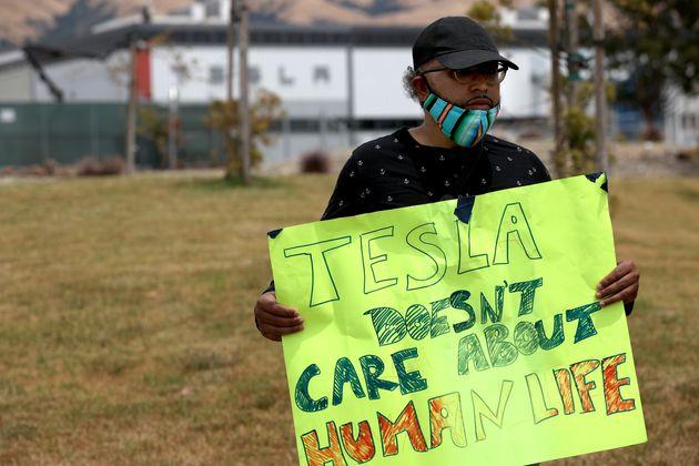 Carlos Gabriel, trabajador de Tesla, sostiene un cartel en una manifestación frente a la planta de Tesla en Fremont, California, ...