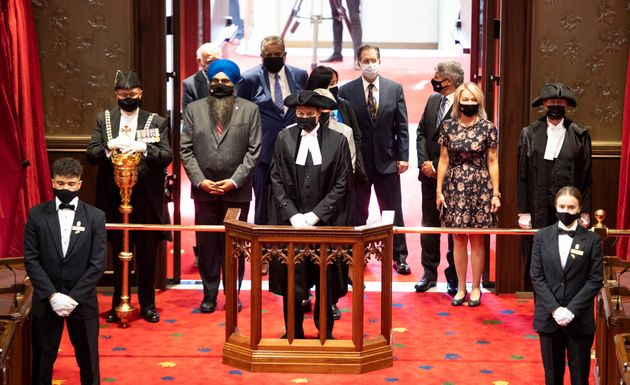 Speaker of the House of Commons Anthony Rota (centre) stands with Members of Parliament to listen to...