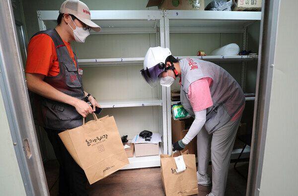 23일 오후 서울 마포구 포은로 망원시장 놀장 픽업센터에서 고형락 배달매니저(오른쪽)와 박세홍 픽업매니저가 시장에서 가지고 온 물건을 창고에서 배달 봉투에 담고 있다.