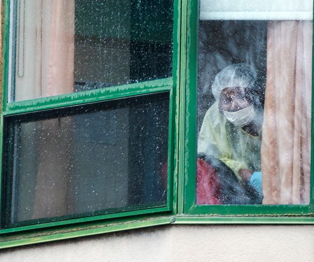 A person wearing protective equipment looks out of a window at the Herron seniors residence on April...