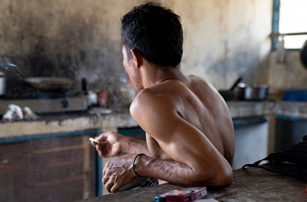 An Indonesian migrant worker rests after working on a palm oil plantation run by the government-owned...