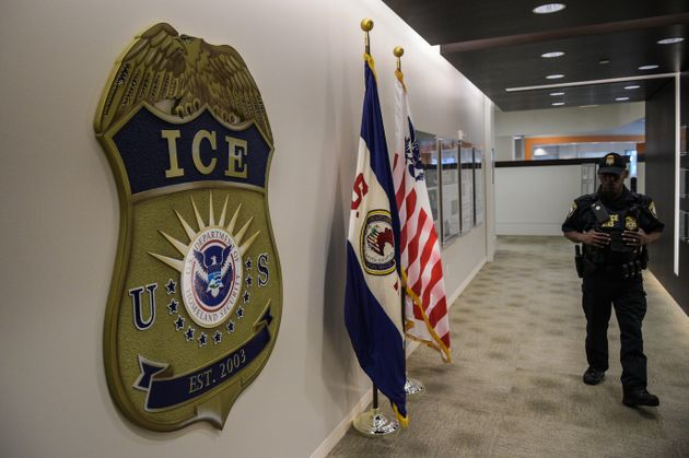 A law enforcement officer walks past ICE logo ahead of a press conference on  May 11,
