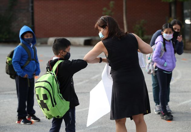 A teacher greets a student at Our Lady of Lourdes Catholic School in