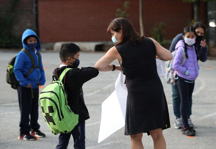 A teacher greets a student at Our Lady of Lourdes Catholic School in Toronto.