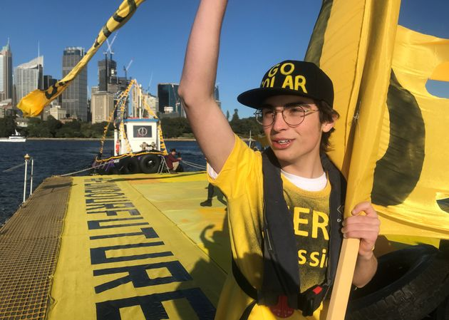 Ambrose Hayes, a 15-year-old climate change activist, rides on a barge during an event as part of the...