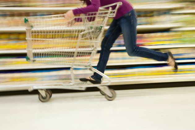 Woman riding grocery cart in supermarket