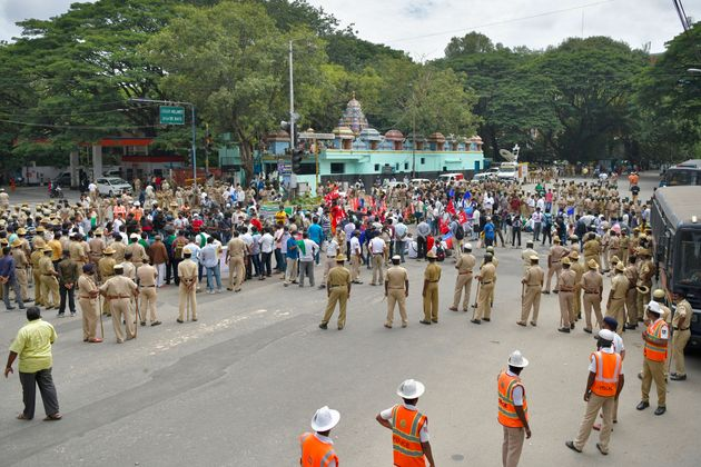 Police personnel stand guard as farmers' organisations stage a protest following in