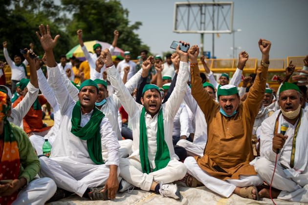 Farmers shout slogans as they block a highway during a protest in Noida against new farm
