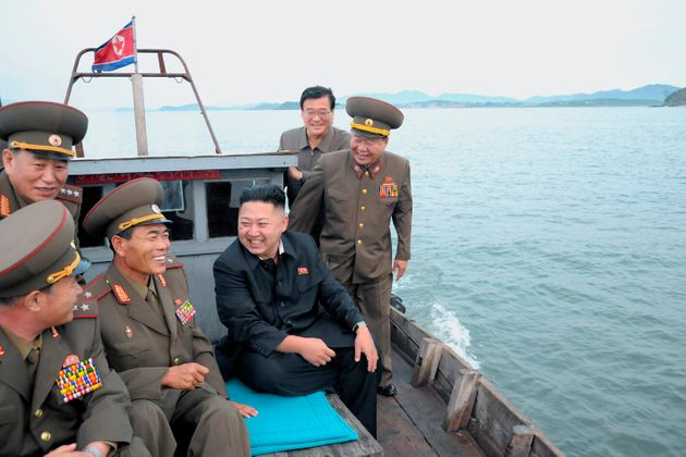 North Korean leader Kim Jong-Un (C) sits in a wooden boat with other soldiers as he visits military units...