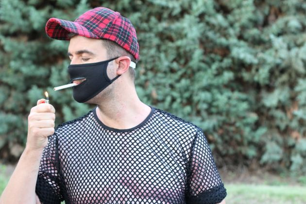 Smoker wearing protective mask with a