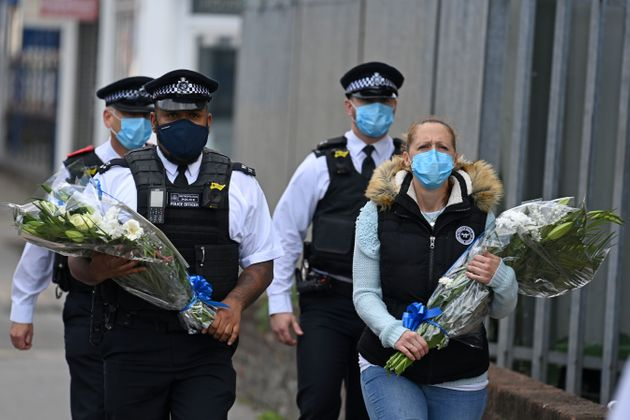 Police officers wearing protective face masks bring floral tributes to the Croydon Custody Centre where...