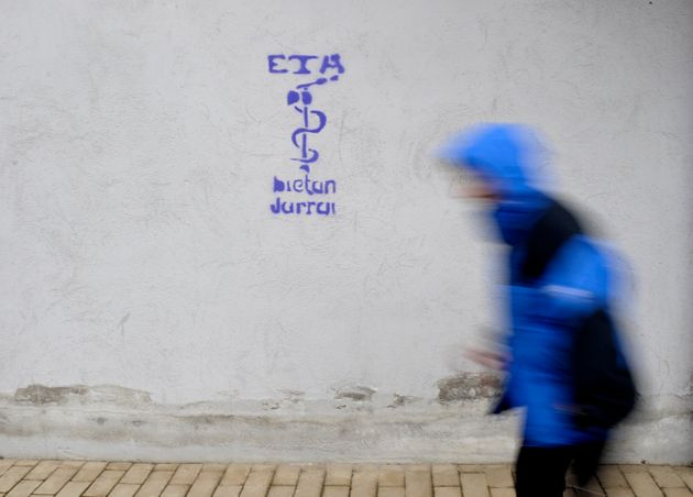 A man walks past the serpent and hatchet anagram of armed Basque separatists ETA ( Euskadi Ta Askatasuna-...