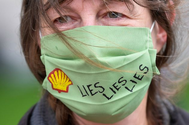 A slogan is seen on a protective face mask of an Extinction Rebellion climate action group protester...