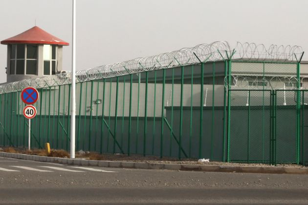 In this Dec. 3, 2018, file photo, a guard tower and barbed wire fences surround an internment facility...