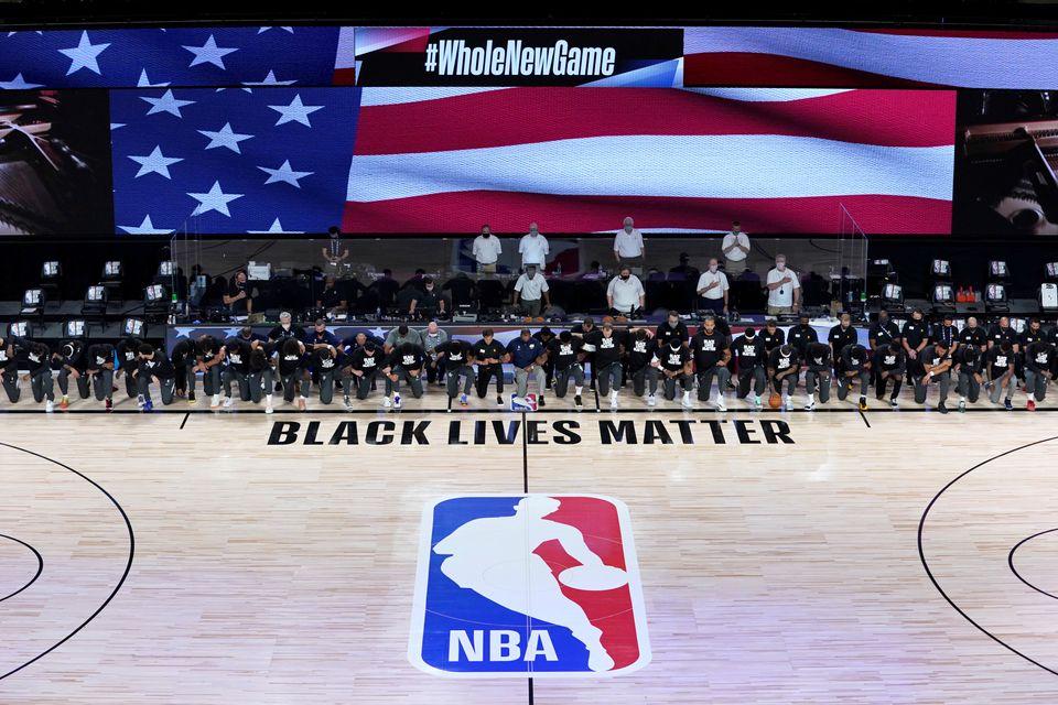 Membros do New Orleans Pelicans e do Utah Jazz ajoelham-se em torno do logotipo do