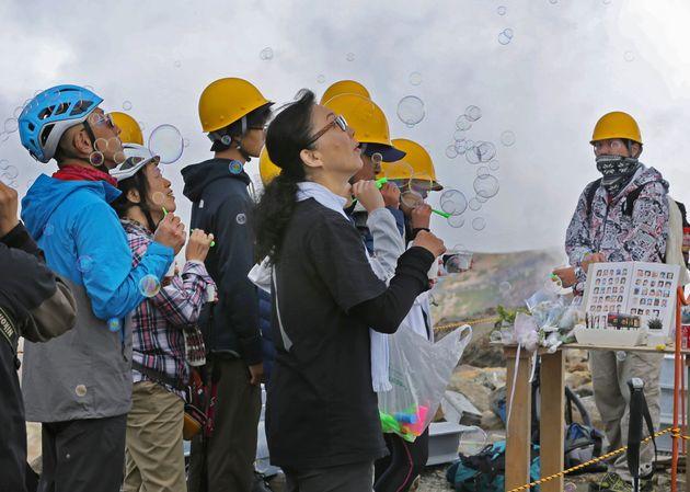 御嶽山の剣ケ峰で、献花台を囲みシャボン玉を飛ばす遺族=2018年9月26日