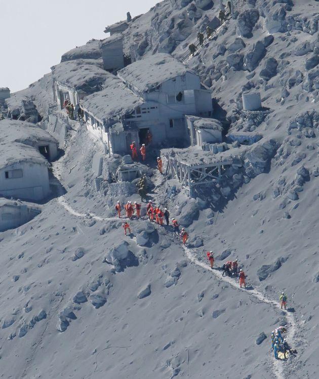 噴火翌日、御嶽頂上山荘に到着した救助隊。灰が積もり、山荘の屋根には噴石による穴が開いている=2014年9月28日、御嶽山上空[時事通信社ヘリより]