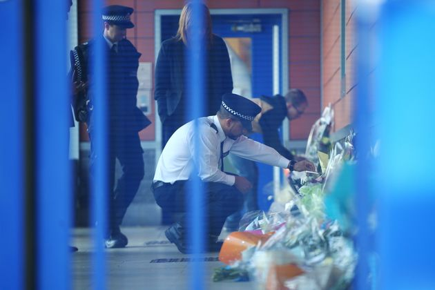 A Metropolitan Police officer looks at floral tributes inside Croydon Custody Centre on September