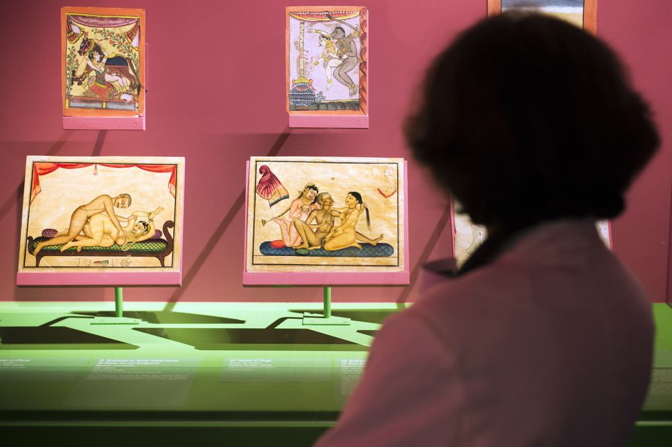 A woman looks at paintings as she visits the exhibition The Kama-Sutra : spirituality and erotism in Indian art, at the Paris' pinacotheque on October 1, 2014 in Paris. The exhibition takes place from October 2 2014 until January 11, 2015.  AFP PHOTO / LIONEL BONAVENTURE        (Photo credit should read LIONEL BONAVENTURE/AFP via Getty Images)