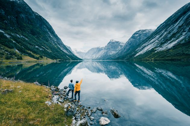 Friends admiring the view on the banks of a norwegian fjord,