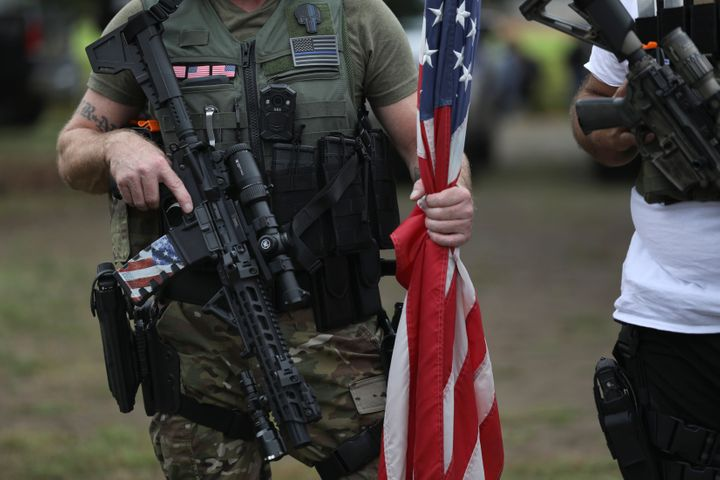 A person holds a weapon and a flag as members of the Proud Boys and other right-wing demonstrators gather in Portland. Thousa