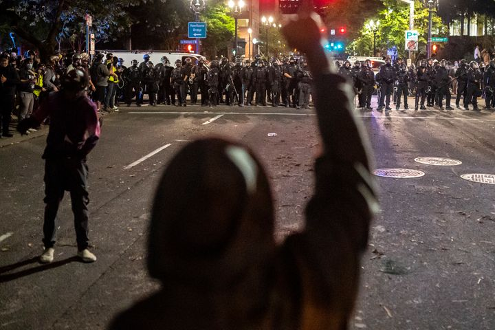 Anti-racism protesters and police face off in the streets of Portland on Saturday. More than a dozen people were arrested.