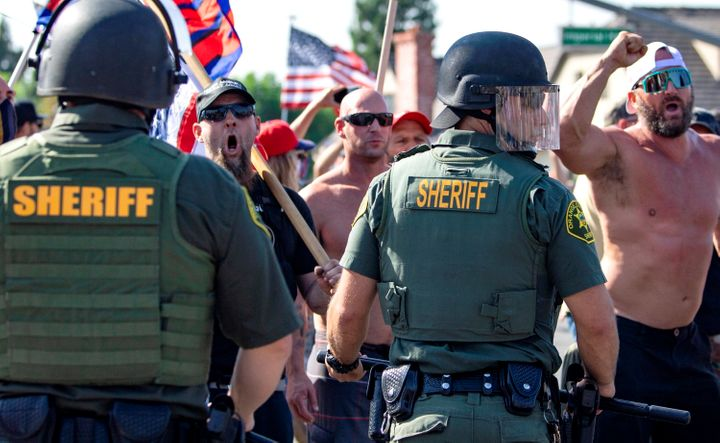 Orange County Sheriff deputies keep protesters and counter protesters apart during demonstrations in Yorba Linda, Calif., on
