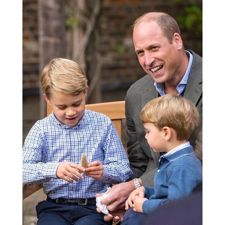 Prince George holds a shark tooth, as his father Prince William and brother Prince Louis look on.