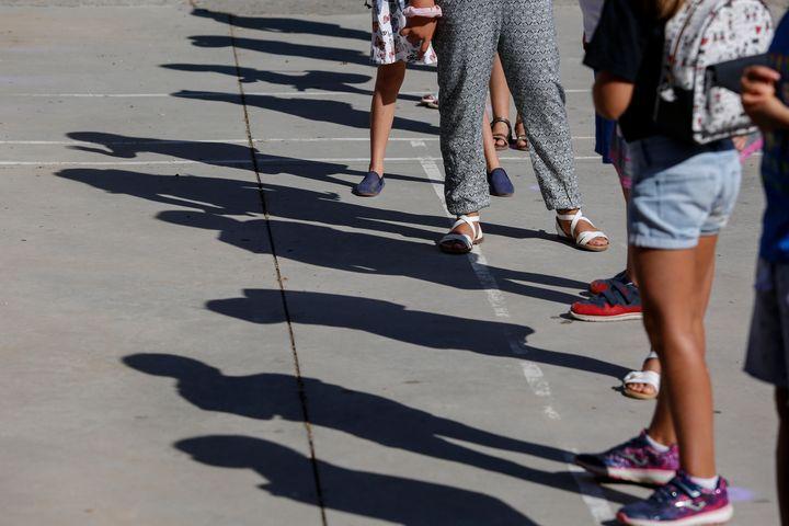 Una fila de niños espera para entrar a su cole, en Granada.