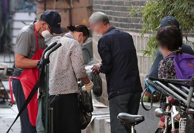 신종 코로나바이러스 감염증(코로나19)가 장기화 되면서 문을 닫는 무료급식소가 늘어나고 있는 가운데 10일 오전 서울 종로구 원각사 무료급식소 앞에서 어르신들이 주먹밥을 받기 위해...
