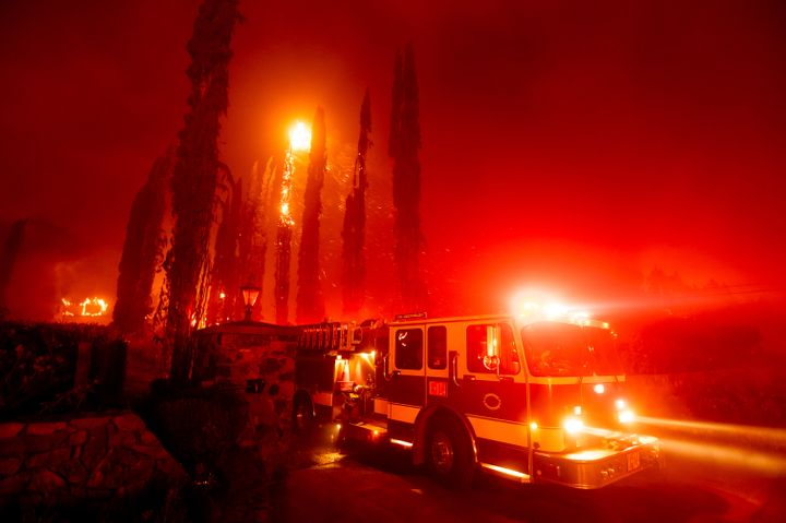A fire engine leaves a burning property as the Glass Fire tears through St. Helena, Calif., on Sunday, Sept. 27, 2020. (AP Ph