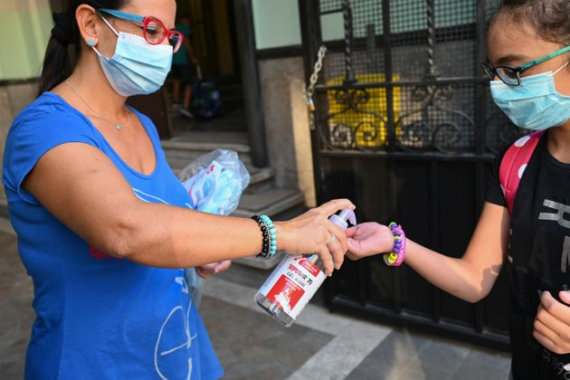 A shool staff (L) wearing a face mask dispenses hand sanitizer gel to a pupil, also wearing a face mask,...