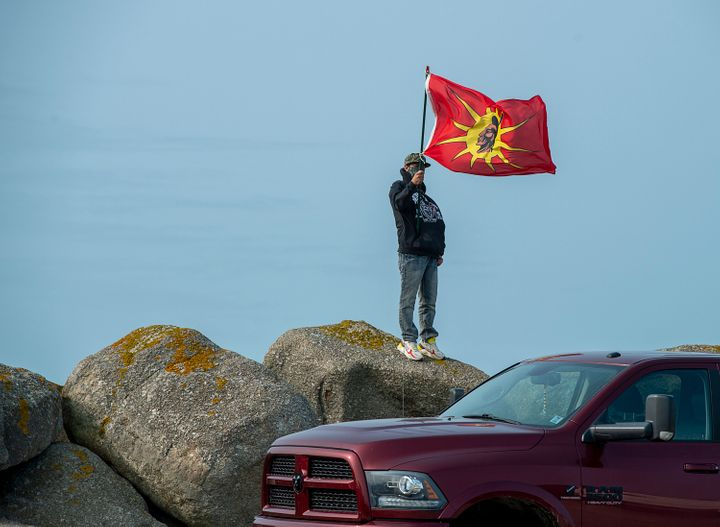 A man flies a warrior flag as members of the Sipekne'katik First Nation gathered on the wharf in Saulnierville, N.S. on Sept. 17, 2020.