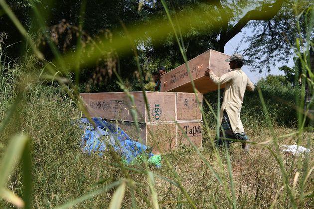 Homem carrega caixões de baixo custo em Nova Déli, na Índia. País ultrapassou...