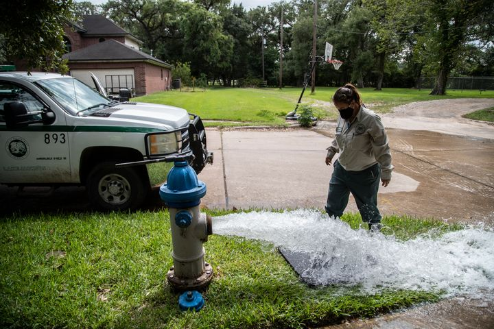 A Lake Jackson water waste operator flushes water from a fire hydrant on Monday in Lake Jackson, Texas, after a brain-eating