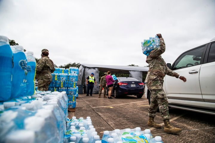 National Guard soldiers and local government employees distribute bottled water to residents in Lake Jackson on Monday. Texas