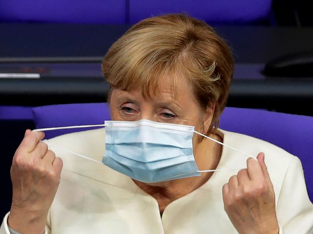 German Chancellor Angela Merkel adjust her face mask during a budget debate as part of a meeting of the...