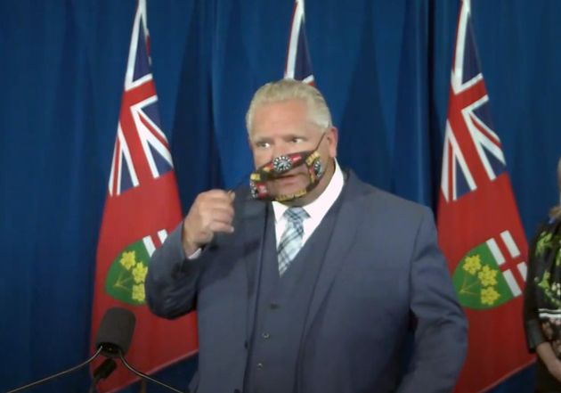 Ontario Premier Doug Ford takes off his face mask during a press conference at Queen's Park in Toronto...