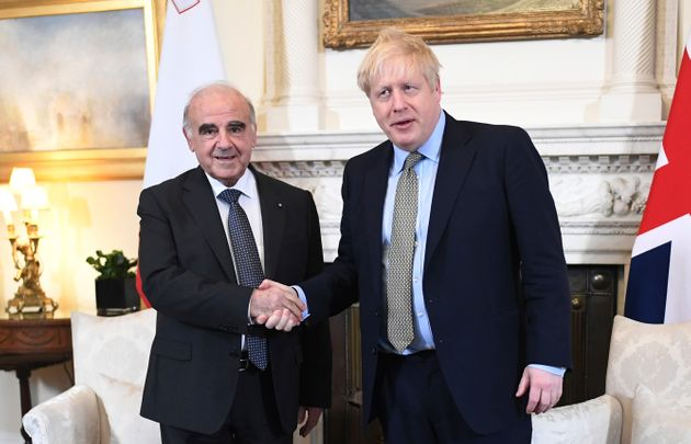 Boris Johnson poses for a handshake with the president of Malta. George Vella, at Downing Street on March 5.