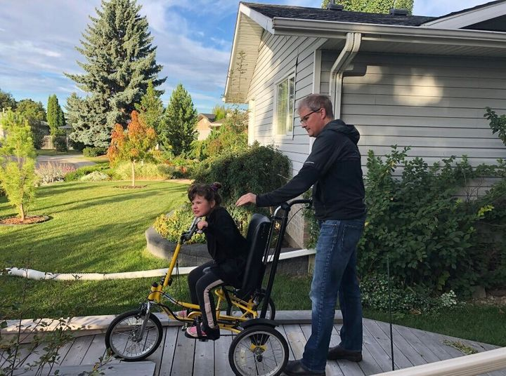 Duane Froese and Annika head to school, on her adapted bike.