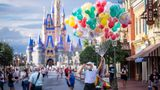 A balloon vendor wears a required face mask due to the Covid-19 pandemic on Main Street, U.S.A. in front of Cinderella Castle at Walt Disney World Resort's Magic Kingdom on Wednesday, August 12, 2020, in Lake Buena Vista, Fla. (Photo by Charles Sykes/Invision/AP)