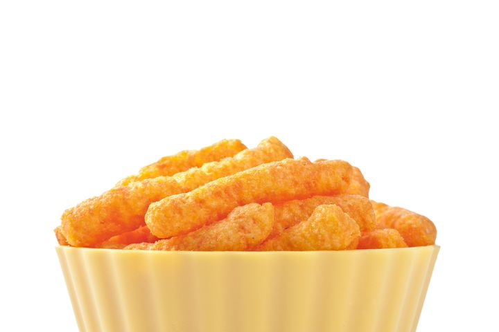 A bowl of puffed cheese snacks.