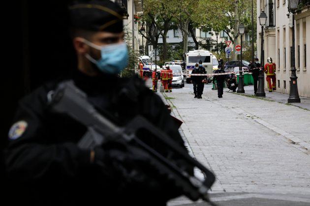 Un policier stationne devant les anciens locuax de Charlie Hebdo, où un homme a attaqué...