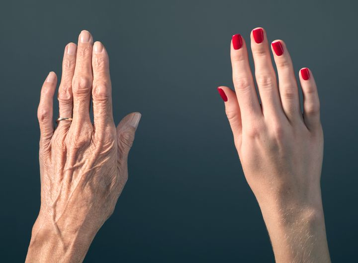 Studio photograph of elderly woman's hand beside a younger woman's hand.